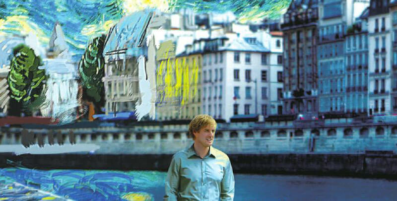 Owen Wilson walks in front of a painted Paris streetscape