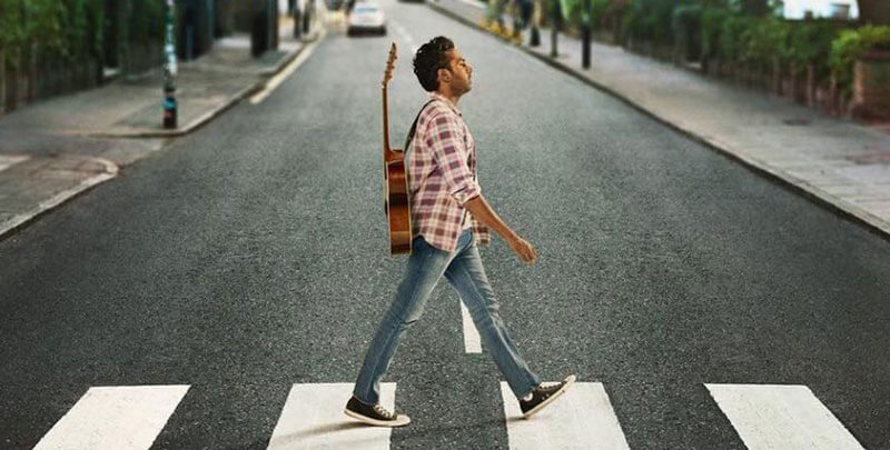 a man with a guitar crosses the famous Abbey Road crosswalk